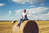 Girl sitting on straw - 210949608