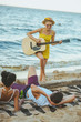 selective focus of young woman playing acoustic guitar for multiethnic friends on sandy beach together