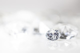 Diamant auf weiß mit Spiegelung vor weißem Hintergrund, mehrere Diamanten in der Unschärfe, Edelsteine mit Textfreiraum - 210959219