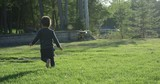 Toddler boy running in grass at sunset - slow motion - 210959257