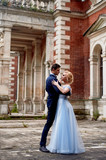 The bride and groom dancing around the columns of the old estate. A tall groom, and a bride with blond hair. Blue wedding dress. Wedding walk and photo shoot - 210965486