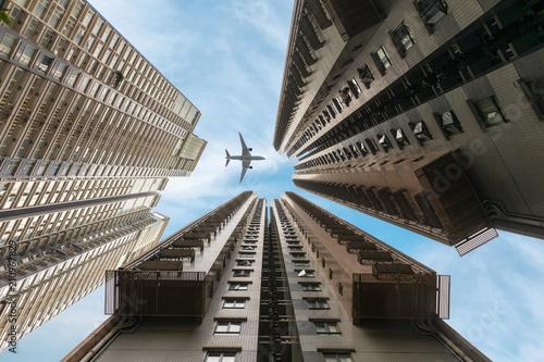Abstrakte Sicht auf die Wolkenkratzer von Hong Kong mit vorbeifliegendem Flugzeug