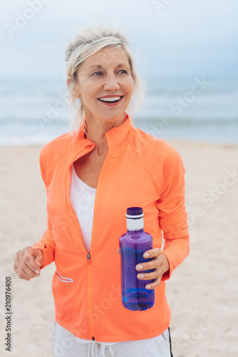 Aluminium Fitness Blond woman exercising on a beach carrying water