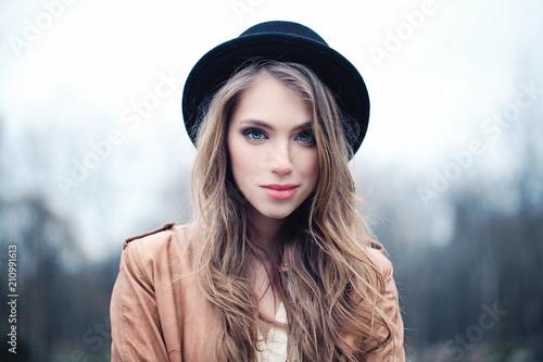 Leinwanddruck Bild Beautiful young woman outdoors in park. Perfect female face closeup