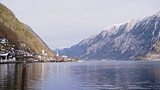 Scenic view from water surface of Hallstatt village placed on lake shore with amazing high mountain ridge on background on sunny winter day in Austria - 210994414