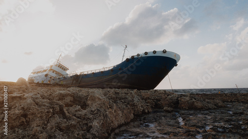 Aluminium Schipbreuk An old sunken abandoned sailing boat standing on the rocky shore. Shipwreck. Beautiful sunset and stormy sea with waves. Malta.