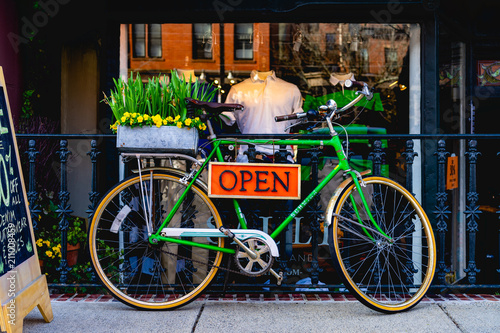 Plexiglas Fiets Vintage green bike with an open sign in front of a store