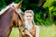 Blond woman with blue eyes with her horse. People and animals friendship concept.