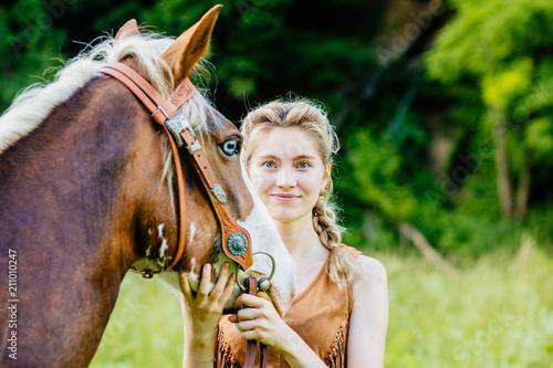 Blond kobieta z niebieskimi oczami z jej koniem. Koncepcja przyjaźni ludzi i zwierząt.
