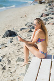 Attractive woman with tablet relaxing on the beach at the ocean or sea