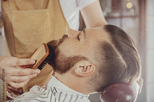 Fototapeta samoprzylepna The barber combs the man's beard with a brush. Photo in vintage style