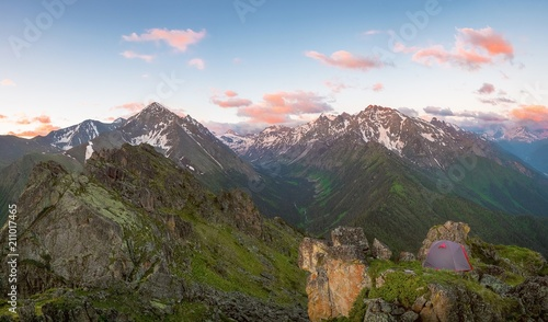 View of the snow-capped mountain tops of Dombay in the early morning and the mountain gorge in the upper summer with bright clouds