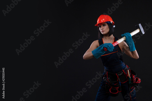 Pretty young woman doing repairs at home. Portrait of a female construction worker. Building, repair concept. - 211035445