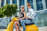 Beautiful couple - handsome stylish guy dressed in a white shirt and jeans and charming blonde woman wearing black dress sitting together on a yellow classic Italian scooter against a skyscraper - 211038643