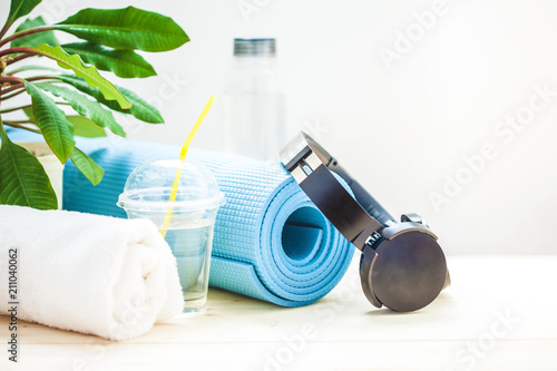 set for sports. Blue yoga mat towel headphones and a bottle of water on a light background The concept of a healthy lifestyle Copy space. © Natalya