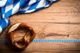 Brezel mit bayrischem Tischtuch auf Holzuntergrund