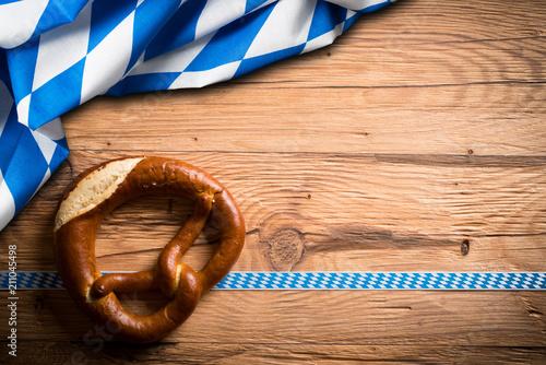 Leinwandbild Motiv Brezel mit bayrischem Tischtuch auf Holzuntergrund