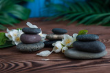 Pyramids of gray zen stones with beautiful fresh white flowers. Concept of harmony, balance and meditation, spa, massage, relax - 211049235