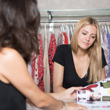 Two women choosing clothes from a catalogue in a shop - 211054254