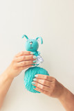 Handmade knitting toy. Female hands with a beautiful blue manicure hold threads and a toy. Soft focus. White background. Free space for text. Concept. - 211054429