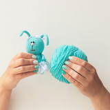 Handmade knitting toy. Female hands with a beautiful blue manicure hold threads and a toy. Soft focus. White background. Free space for text. Concept. - 211054434