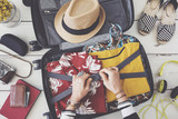 Woman hand preparing summer luggage