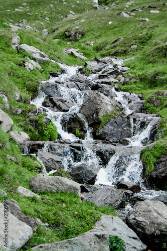 Mountain river with a waterfall among green grass and stones in Romania, Transfagarasan - 211056661