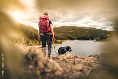 Leinwanddruck Bild young woman with backpack and german shepherd dog puppy standing on mountain in front of forest and lake
