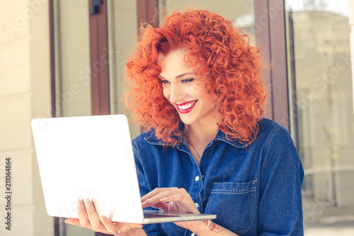 woman sitting outside and working on laptop.
