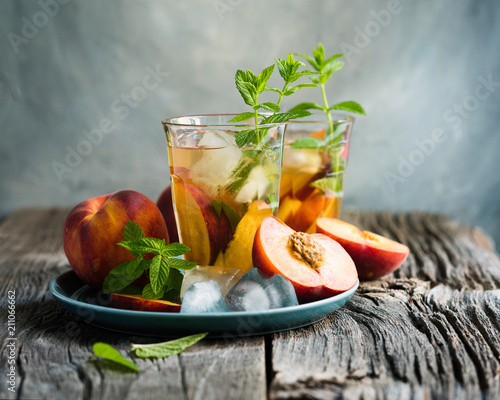 Fototapeta Refreshing iced tea with ripe peaches on rustic background, selective focus, toned image