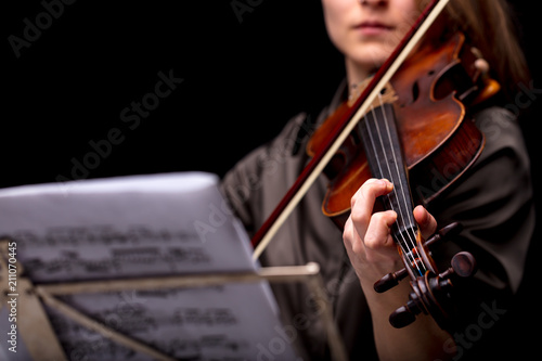 violinist playing in front of her score - 211070445