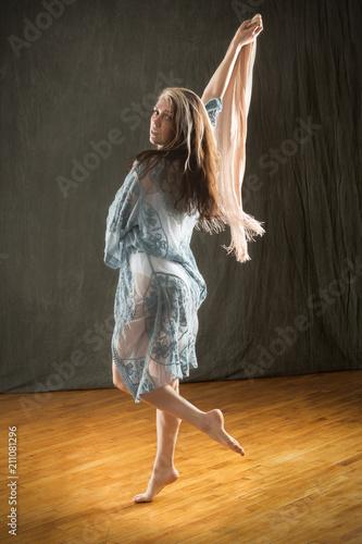 Studio shot of barefoot dancer in blue cape and leotard.