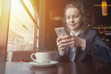 Young business woman writing a message on smart phone and smiling at cafe - 211083854