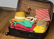Collected suitcase for travel. Suitcase in open view closeup with things to rest on a wooden background