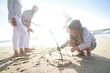 Leinwanddruck Bild - Family having fun writing messages on sandy beach