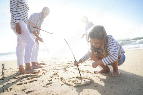 Leinwanddruck Bild Family having fun writing messages on sandy beach