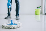 Husband housekeeping and cleaning concept, Happy young man in blue rubber gloves wiping dust using mop while cleaning on floor at home - 211095442