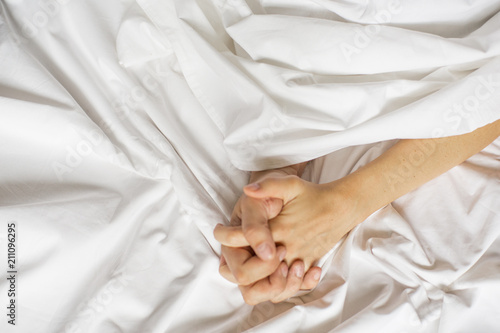 Sensual beautiful young couple is having sex on bed. Female hand pulling white sheets in ecstasy, orgasm. Love concept. Wellness. Couple in love. Orgasm concept - 211096295