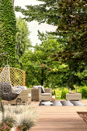 Hanging chair and garden furniture on terrace near trees during summer. Real photo - 211099830