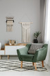 Real photo of a boho living room interior with macrame hanging on gray wall behind a comfy, green armchair with a cushion