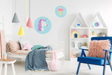 Furry pink pillow on a vibrant blue armchair in a sweet kid bedroom interior with cozy bedding and cartoon posters on white walls - 211100287