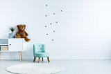 Small light blue armchair for kid standing in white room interior with stars on the wall, white rug and cupboard with books, teddy bear and fresh plant. Empty space for your crib - 211101010