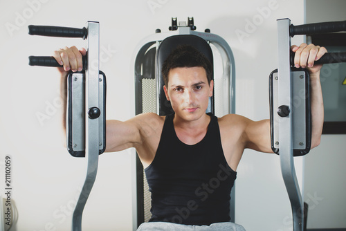 Young strong man doing exercises on the simulator at the gym. Toned image