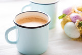 Latte in a blue enamel cup with colorful eggs and flowers in the background. Close up. Spring. - 211115491