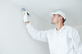 Painting. Painter with paint brush covering ceiling angle with white paint