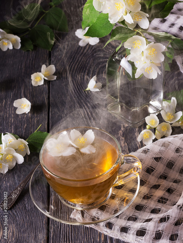 Steam over Cup of hot tea, Jasmine flowers are scattered on grey surface