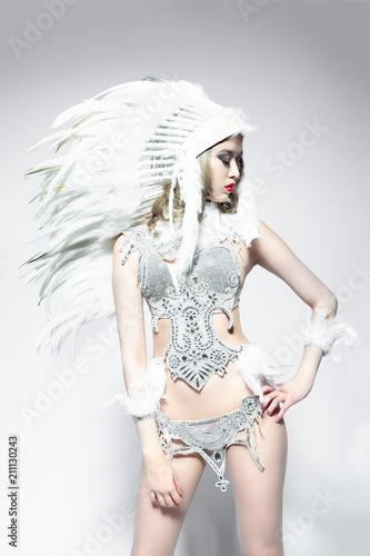 Asiatisch wirkende frau mit federschmuck und einem glamouroutfit  als showgirl - 211130243