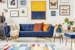 Painting above navy blue couch in artistic living room interior with colorful rug. Real photo
