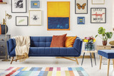 Painting above navy blue couch in artistic living room interior with colorful rug. Real photo - 211132630