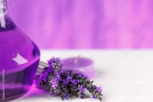 Leinwanddruck Bild Spa products, aroma candle and lavender flowers on a wooden background